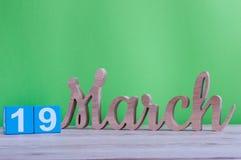 Mars 19th Dag 19 av månaden, daglig träkalender på tabellen och gräsplanbakgrund den förorts- dagskogfjädern går Jordtimme och Arkivfoton