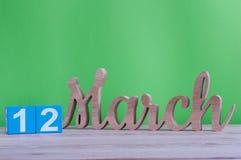 Mars 12th Dag 12 av månaden, daglig träkalender på tabellen och gräsplanbakgrund Vårdagen, tömmer utrymme för text Arkivbild