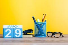 Mars 29th Dag 29 av månaden, kalender på ljus - gul bakgrund, arbetsplats med kontorssuplies Vårtid som är tom Fotografering för Bildbyråer