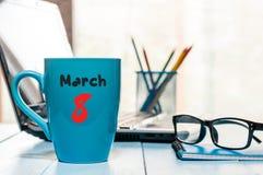 Mars 8th Dag 8 av månaden, kalender på morgonkaffekoppen, bakgrund för affärskontor, arbetsplats med bärbara datorn och exponerin Royaltyfri Bild