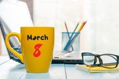 Mars 8th Dag 8 av månaden, kalender på morgonkaffekoppen, bakgrund för affärskontor, arbetsplats med bärbara datorn och exponerin Royaltyfri Foto
