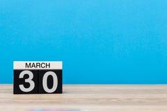Mars 30th Dag 30 av månaden, kalender på tabellen med blå bakgrund Vårtid, tömmer utrymme för text Royaltyfri Foto