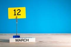 Mars 12th Dag 12 av marschmånaden, kalender på liten etikett på blå bakgrund Fjädra den tid… ron lämnar, naturlig bakgrund Töm ut Royaltyfri Bild