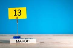 Mars 13th Dag 13 av marschmånaden, kalender på liten etikett på blå bakgrund Fjädra den tid… ron lämnar, naturlig bakgrund Töm ut Arkivbilder