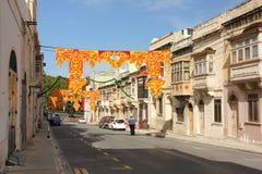Marsa, Malta - em maio de 2018: Rua festiva decorada com polícias e os balcões tradicionais velhos Bandeiras para o religio anual fotos de stock