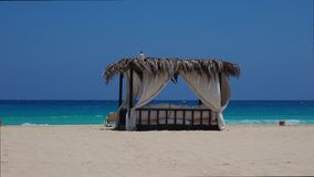 Marsa Matruh, Egypt. Elegant gazebo on the beach. Amazing sea with tropical blue, turquoise and green colors. Relaxing context. Nobody on the beach. Fabulous stock footage