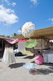 Marsaxklokk market. MARSAXLOKK, MALTA - SEPTEMBER 15, 2015: Shopping market displays with lace umbrellas in popular fishing village on a sunny day in September Stock Photos