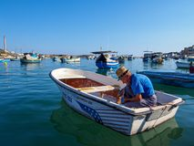 Marsaxlokk,马耳他:10月08日:未认出的老人在Marsaxlokk准备2014年10月08日的渔夫小船,马耳他 图库摄影