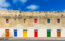 Marsaxlokk,马耳他-有橙色,蓝色,黄色,红色,绿色和棕色门和窗口的传统马尔他葡萄酒房子 免版税图库摄影