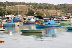 Marsaxlokk, Мальта, август 2016 Многочисленные пестротканые рыбацкие лодки в гавани города стоковые фото