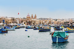 Marsaxlokk. Is a fishermen village in the south of Malta. The colorful boats, called luzzus, are typical for this region.In summer  there are many tourists in Stock Photography