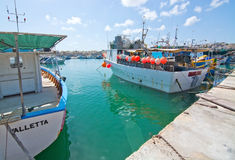 Marsaxlokk boats. MARSAXLOKK, MALTA - SEPTEMBER 15, 2015: Colorful painted small boats moored in the clear turquoise water on a sunny day on September 15, 2015 Royalty Free Stock Photo