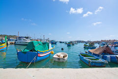 Marsaxlokk boats. MARSAXLOKK, MALTA - SEPTEMBER 15, 2015: Colorful painted small boats moored in the clear turquoise water on a sunny day on September 15, 2015 Royalty Free Stock Image