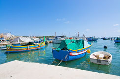 Marsaxlokk boats. MARSAXLOKK, MALTA - SEPTEMBER 15, 2015: Colorful painted small boats moored in the clear turquoise water on a sunny day on September 15, 2015 Royalty Free Stock Photography