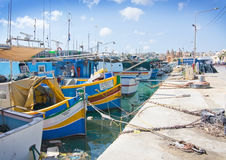 Marsaxlokk boats. MARSAXLOKK, MALTA - SEPTEMBER 15, 2015: Colorfully painted small wooden boats moored along the quay with the Marsaxlokk Parish Church in the Stock Photos