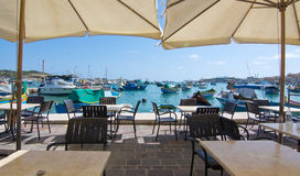 Marsaxlokk boats. MARSAXLOKK, MALTA - SEPTEMBER 15, 2015: Boats moored along the quay in the clear turquoise water of popular fishing village on a sunny day on Royalty Free Stock Photo