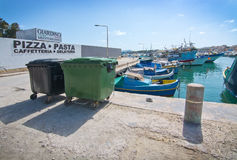 Marsaxlokk boats. MARSAXLOKK, MALTA - SEPTEMBER 15, 2015: Pizza sign, garbage cans and boats along the quay in the clear turquoise water of popular fishing Royalty Free Stock Photo