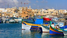 Marsaxlokk fishermen village in Malta. Traditional colorful boats at the port of Marsaxlokk. Marsaxlokk, Malta island. Traditional fishing boats luzzus with stock photography