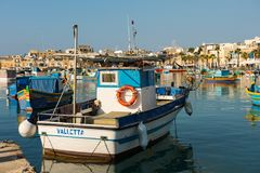 Marsaxlokk fishing village harbor with boats. MARSAXLOKK, MALTA - AUGUST 23, 2017: Traditional colorful luzzu fishing boats arriving and anchoring early in the Royalty Free Stock Photography