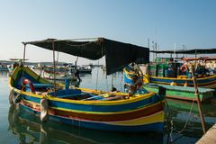 Marsaxlokk fishing village harbor with boats. MARSAXLOKK, MALTA - AUGUST 23, 2017: Traditional colorful luzzu fishing boats arriving and anchoring early in the Stock Images