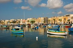 Marsaxlokk fishing village harbor with boats. MARSAXLOKK, MALTA - AUGUST 23, 2017: Traditional colorful luzzu fishing boats arriving and anchoring early in the Royalty Free Stock Photo