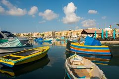 Marsaxlokk fishing village harbor with boats. MARSAXLOKK, MALTA - AUGUST 23, 2017: Traditional colorful luzzu fishing boats arriving and anchoring early in the Royalty Free Stock Photos
