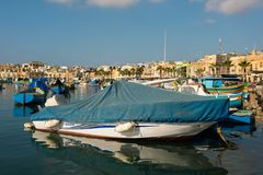 Marsaxlokk fishing village harbor with boats. MARSAXLOKK, MALTA - AUGUST 23, 2017: Traditional colorful luzzu fishing boats arriving and anchoring early in the Stock Photography