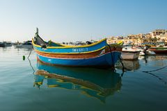 Marsaxlokk fishing village harbor with boats. MARSAXLOKK, MALTA - AUGUST 23, 2017: Traditional colorful luzzu fishing boats arriving and anchoring early in the Stock Photo