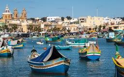 Marsaxlokk-Hafen mit traditionellen, bunten Luzzu-Booten in der Bucht mit Markt im Hintergrund lizenzfreie stockbilder