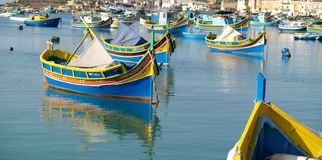 Marsaxlokk harbor. Colorful traditional fishermans wooden boats Luzzu in the bay of Marsaxlokk. Malta Royalty Free Stock Photo