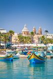 Marsaxlokk harbour and church. Traditional colourful Maltese Luzzu fishing boats in the turquoise blue water of Marsaxlokk harbour, with the beautiful Parish Stock Photo