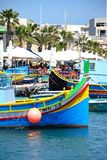 Marsaxlokk harbour, Malta. Traditional Maltese Dghajsa fishing boats in the harbour with waterfront buildings and restaurants to the rear, Marsaxlokk, Malta Stock Photo