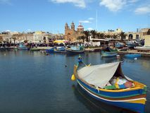 Marsaxlokk, Malta. Famous market day at the fishing village of Marsaxlokk in Malta.  Colourful fishing boats and market stalls around the harbour Royalty Free Stock Photo