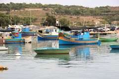 Marsaxlokk, Malta, August 2016. Numerous multi-colored fishing boats in the harbor of the city. stock photos