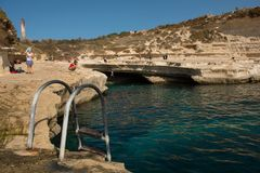 Saint Peter`s pool, Malta. MARSAXLOKK, MALTA - AUGUST 21, 2017: People bathing and relaxing at Saint Peter`s pool, a natural rocky gulf near the sea in Malta Stock Photo