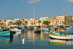 Marsaxlokk fishing village harbor with boats. MARSAXLOKK, MALTA - AUGUST 23, 2017: Traditional colorful luzzu fishing boats arriving and anchoring early in the Royalty Free Stock Image