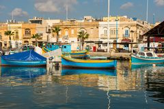Marsaxlokk fishing village harbor with boats. MARSAXLOKK, MALTA - AUGUST 23, 2017: Traditional colorful luzzu fishing boats arriving and anchoring early in the Royalty Free Stock Images