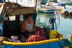 Marsaxlokk fishing village harbor with boats. MARSAXLOKK, MALTA - AUGUST 23, 2017: Traditional colorful luzzu fishing boats arriving and anchoring early in the Stock Photos