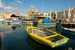 Marsaxlokk fishing village harbor with boats. MARSAXLOKK, MALTA - AUGUST 23, 2017: Traditional colorful luzzu fishing boats arriving and anchoring early in the Stock Image