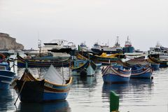 Marsaxlokk, Malta, August 2016. View of large and small fishing boats in the harbor. stock image