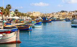 Marsaxlokk fishermen village in Malta. Traditional colorful boats at the port of Marsaxlokk. Marsaxlokk, Malta island. Traditional fishing boats luzzus with royalty free stock photo