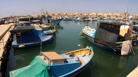 MARSAXLOKK, MALTA - July 6, 2016: Beautiful fishing village architecture with colored boats at anchor in a bay stock video footage