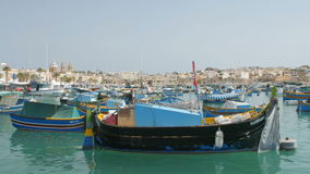 MARSAXLOKK, MALTA - July 6, 2016: Beautiful fishing village architecture with colored boats at anchor in a bay stock video