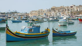 MARSAXLOKK, MALTA - July 6, 2016: Beautiful fishing village architecture with colored boats at anchor in a bay stock footage