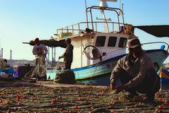 Marsaxlokk/Malta - 7 maggio 2017: Pescatori che raccolgono e che puliscono le reti da pesca dopo il fermo fresco del giorno fotografia stock libera da diritti