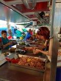 Marsaxlokk, Malta - Mai 2018: Frau mit dem Ingwerhaar wird am fishmarket für Garnelen zahlen stockbild