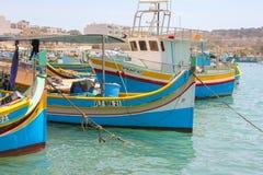 Marsaxlokk Malta - Maj 2018: Härlig sikt av fiskeläget med traditionell synad fartygluzzu royaltyfri bild