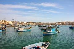 Marsaxlokk Malta - Maj 2018: Panoramautsikt av fiskeläget med traditionell synad fartygluzzu arkivbild