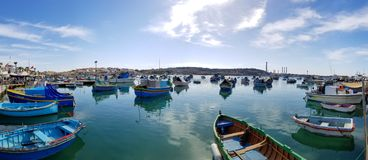 Marsaxlokk, Malta - May 2018: Panoramic view of fishing village with traditional eyed boats luzzu royalty free stock images
