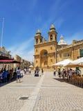 Marsaxlokk, Malta - May 2018: Tourists walking near cafe and Marsaxlokk Parish Church stock photography